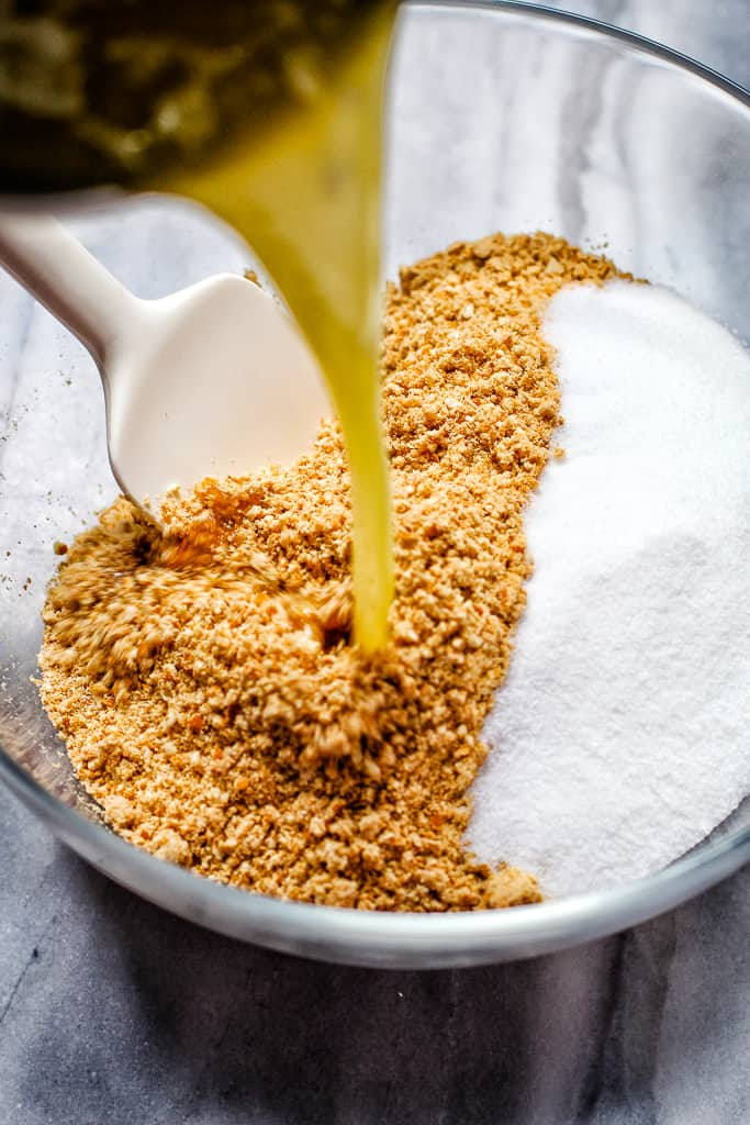 Pouring butter into salted pretzel crust crumbs