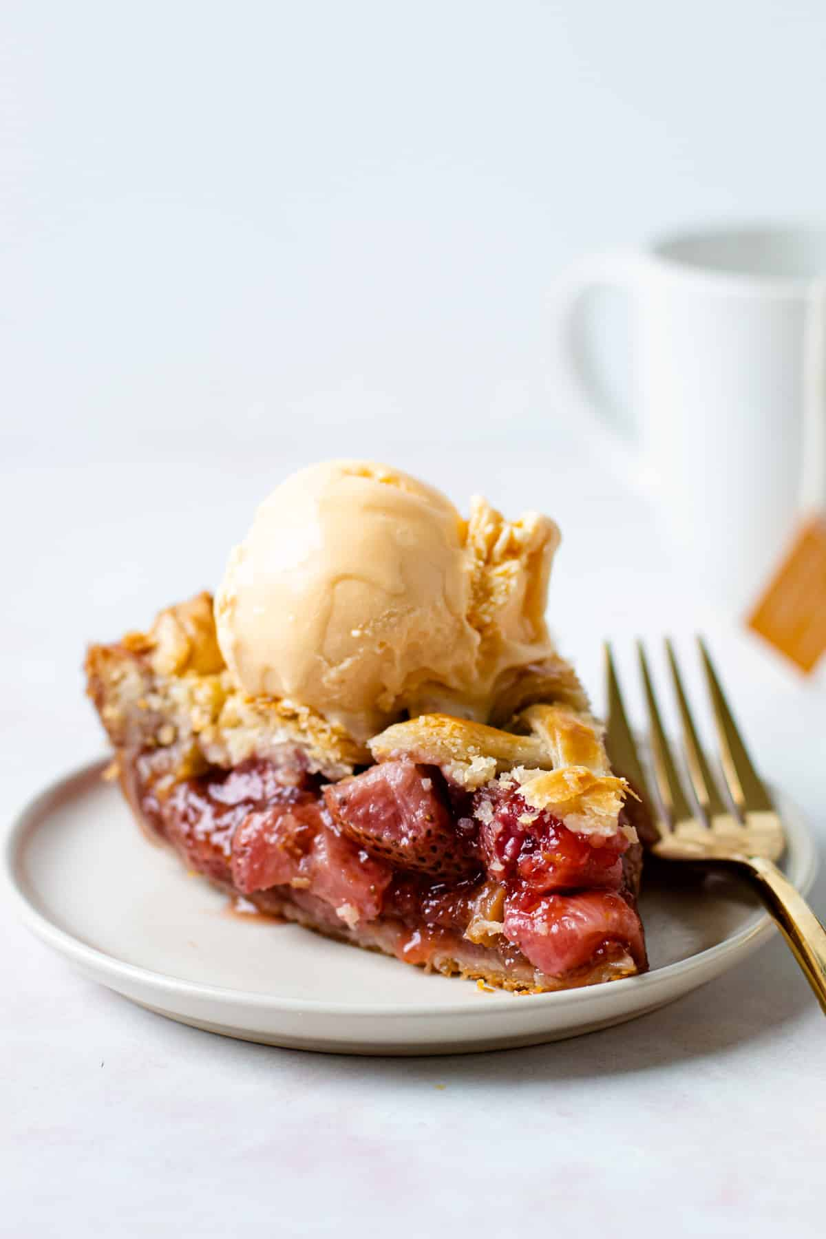 A slice of strawberry rhubarb pie with ice cream on it on a place.