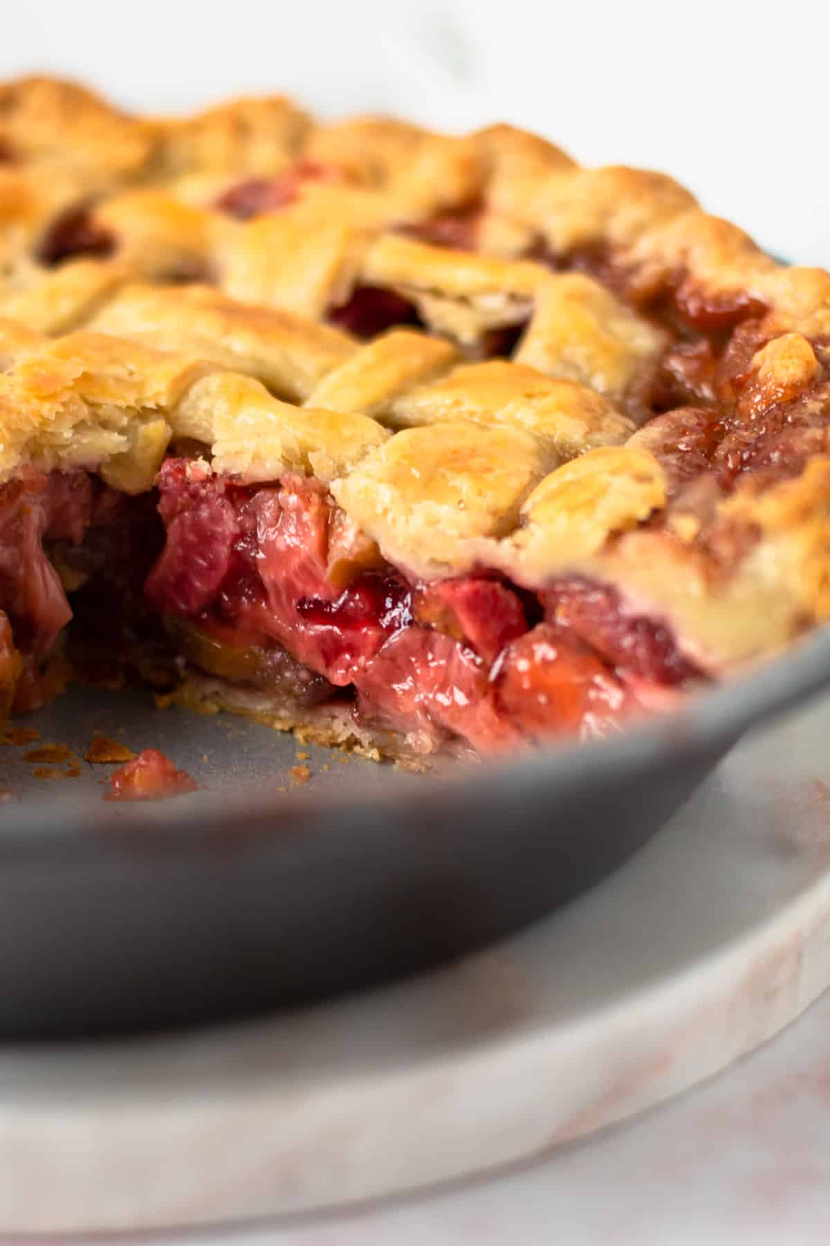 A baked strawberry Rhubarb pie with a slice taken out of it in the pie tin.