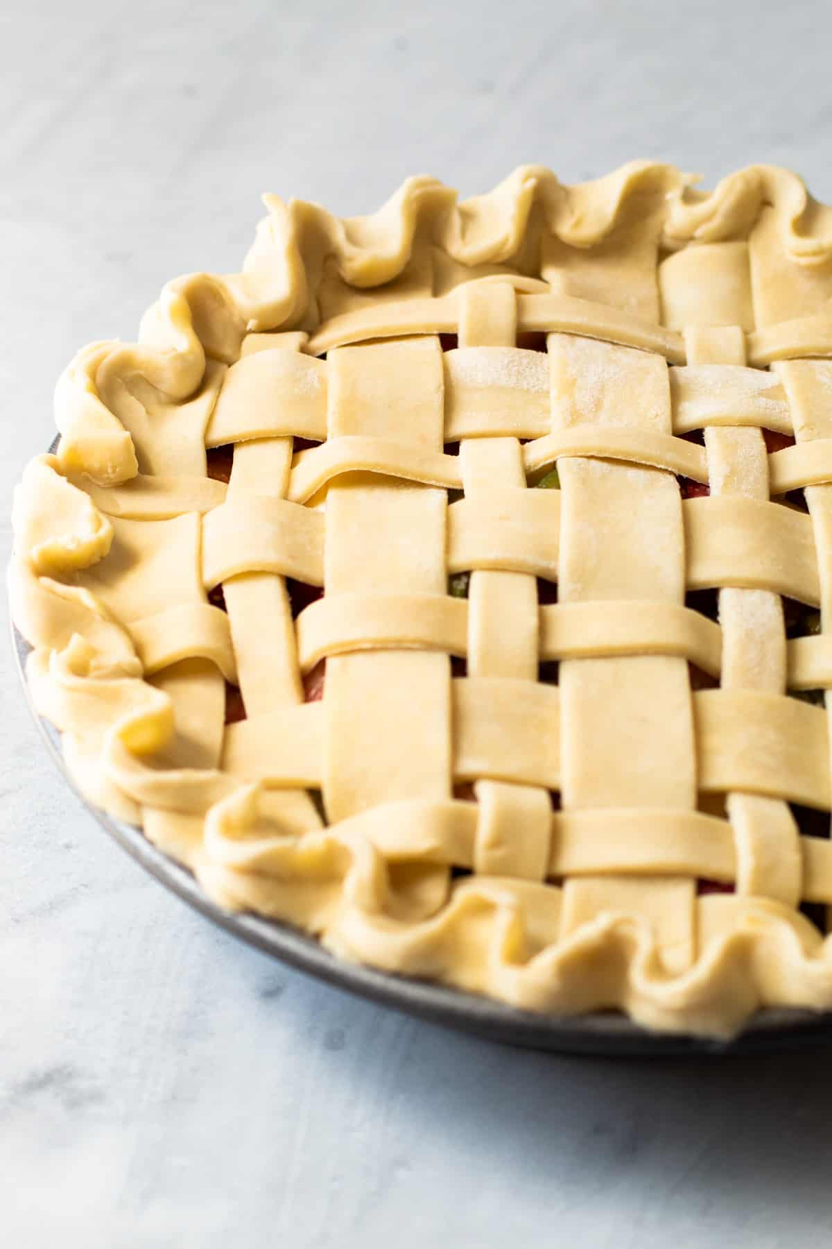 A unbaked pie with a decorative crust.