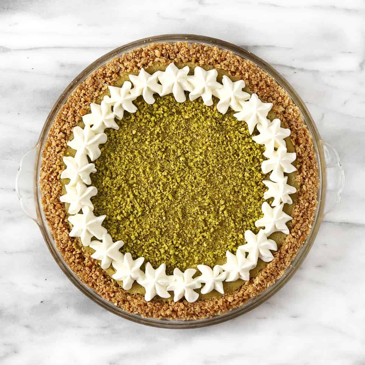 decorated pie with pistachios and whipped cream