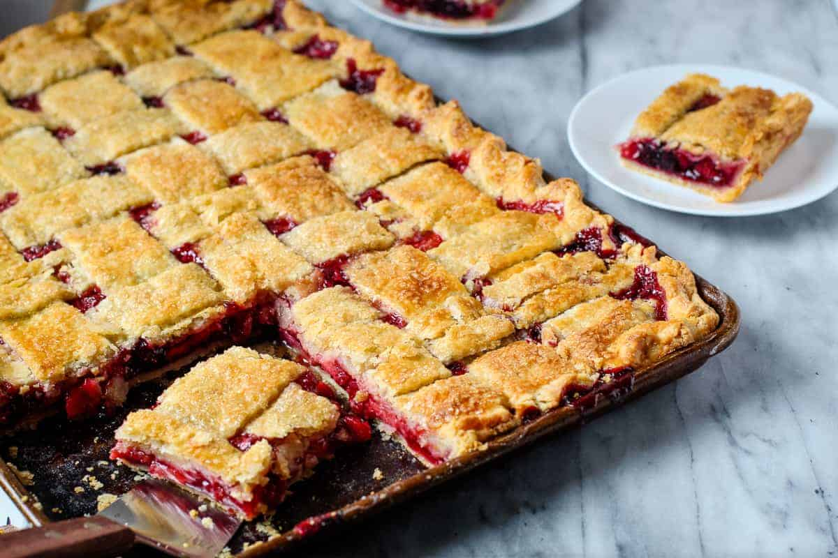 strawberry cherry slab pie with a slice taken out of it