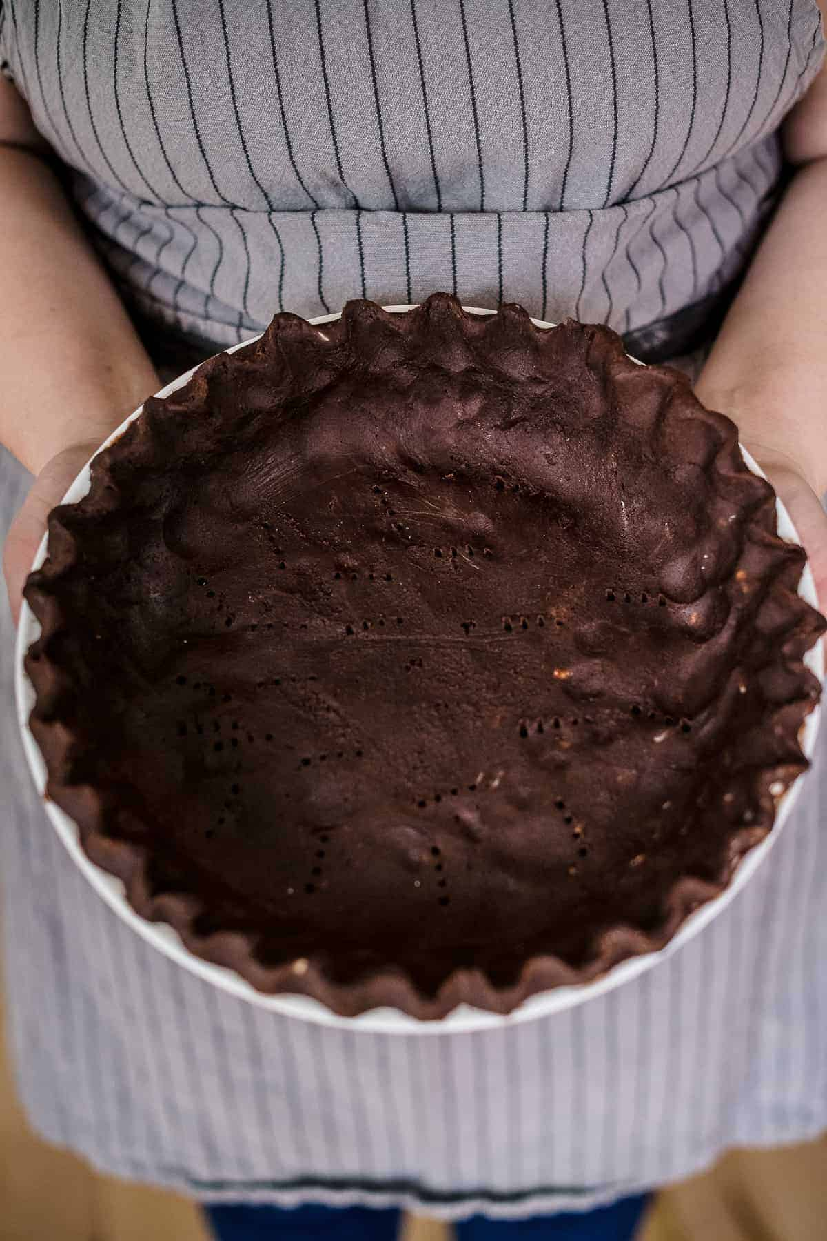 Raw chocolate pie crust in a pie tin with fluted edges