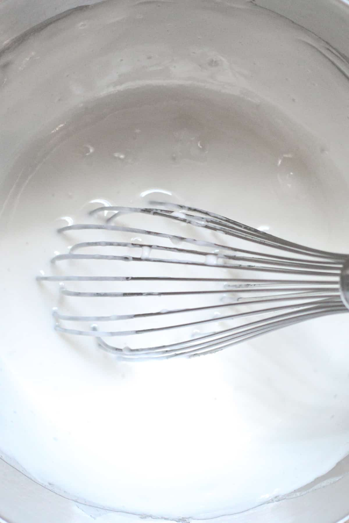 Egg whites and sugar are heated and whisked on a stove.