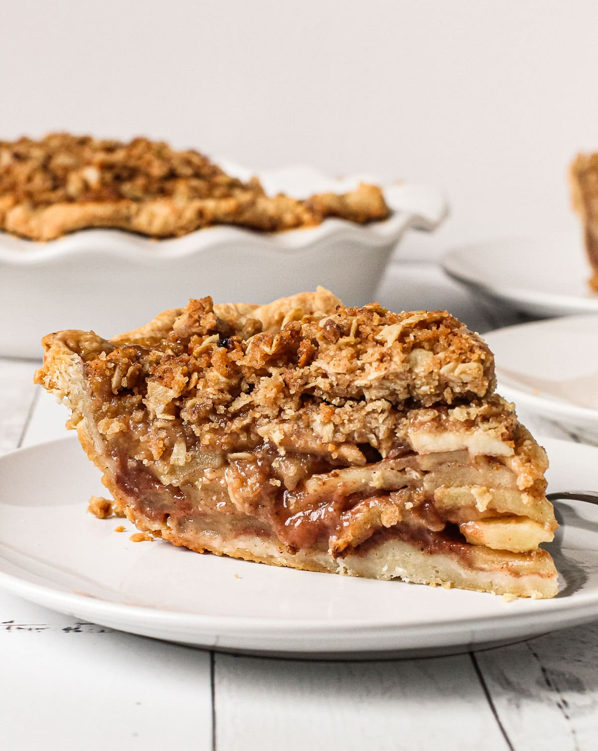 A slice of apple crumb pie on a plate.