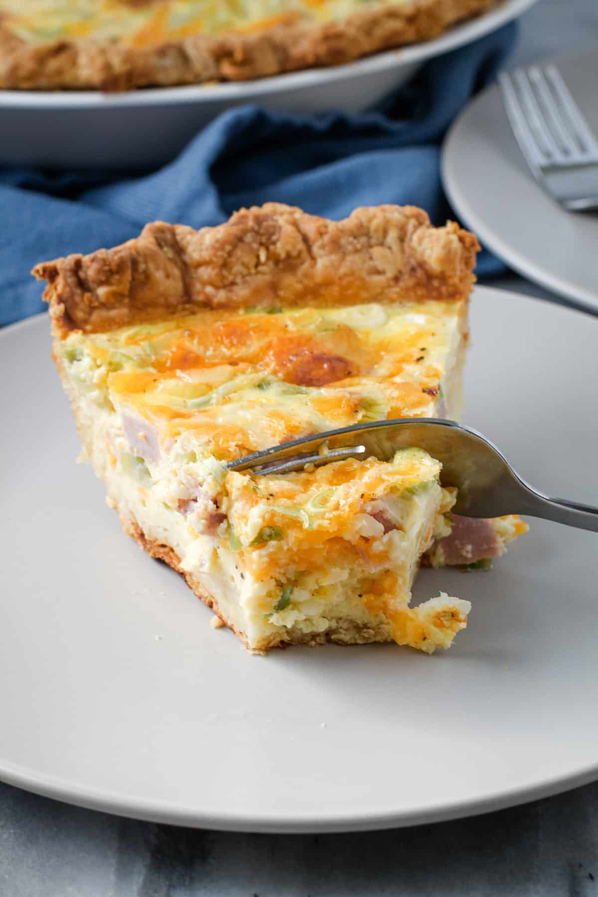 Fork breaking into a ham cheese quiche.