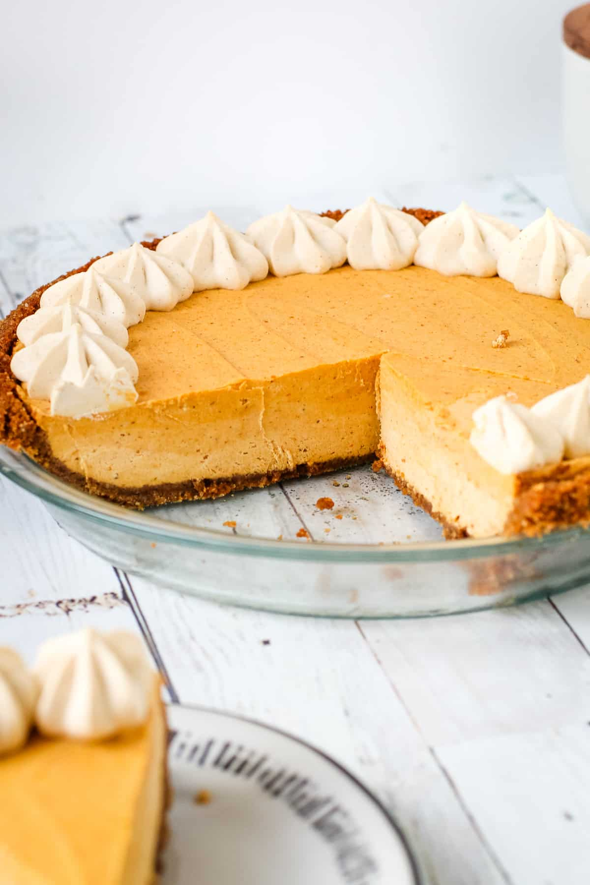 Pumpkin pie with heavy whipped cream recipe with a slice taken out of it.