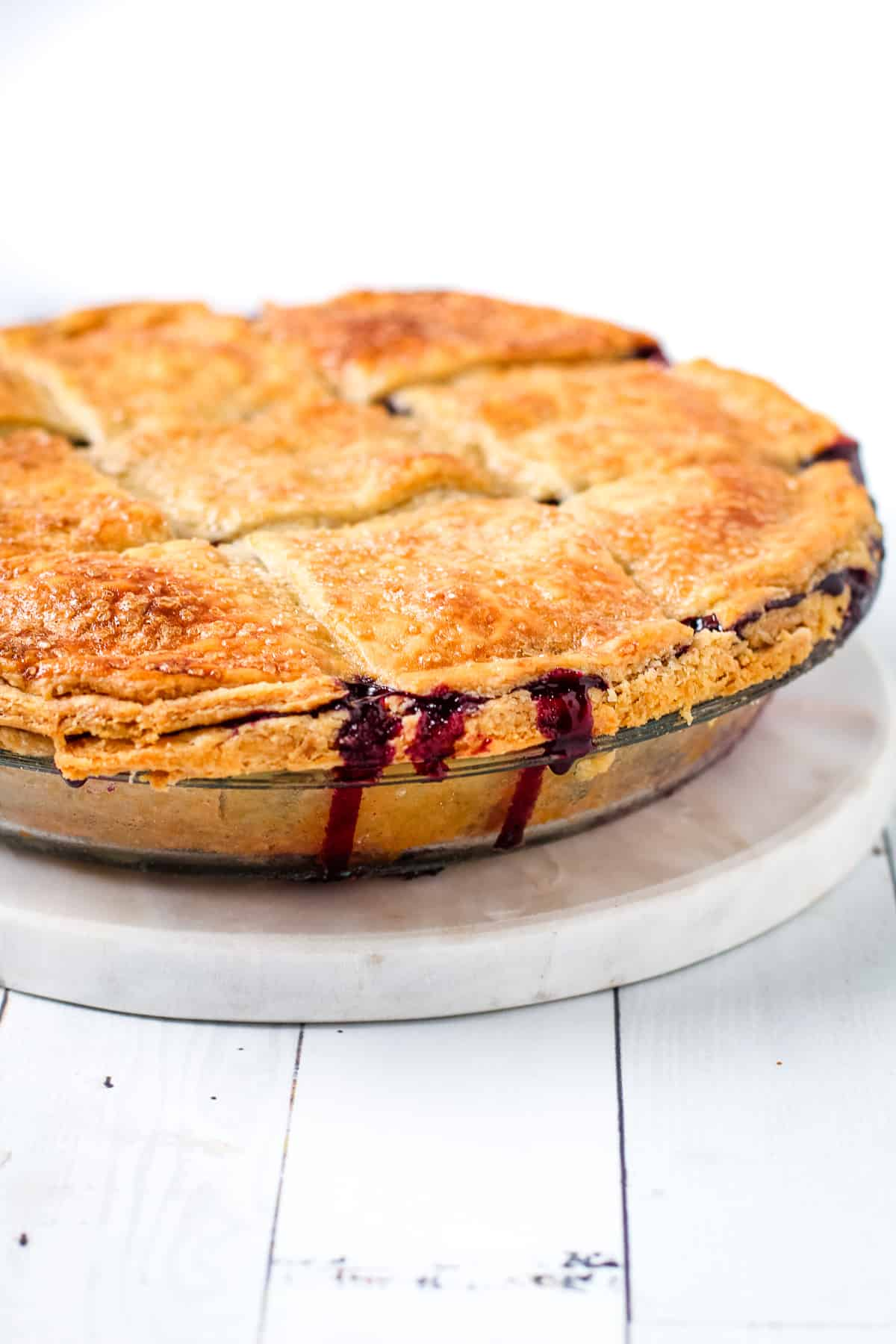 Blueberry and cranberry juices flowing out of a baked pie