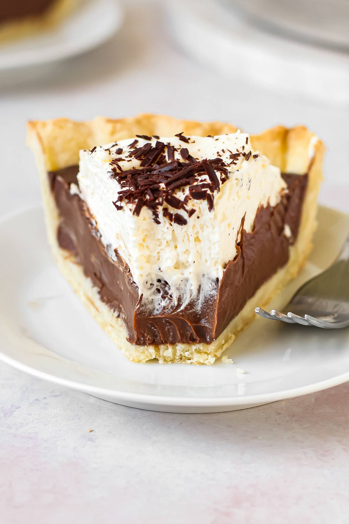 A slice of chocolate cream pie with a forkful taken out of it on a plate.