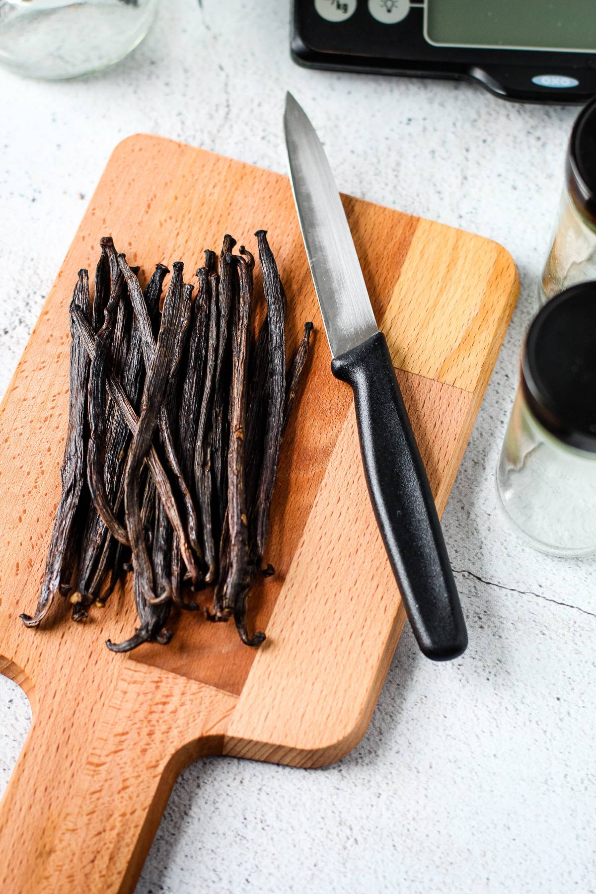 Whole vanilla beans on a cutting board with a pairing knife.
