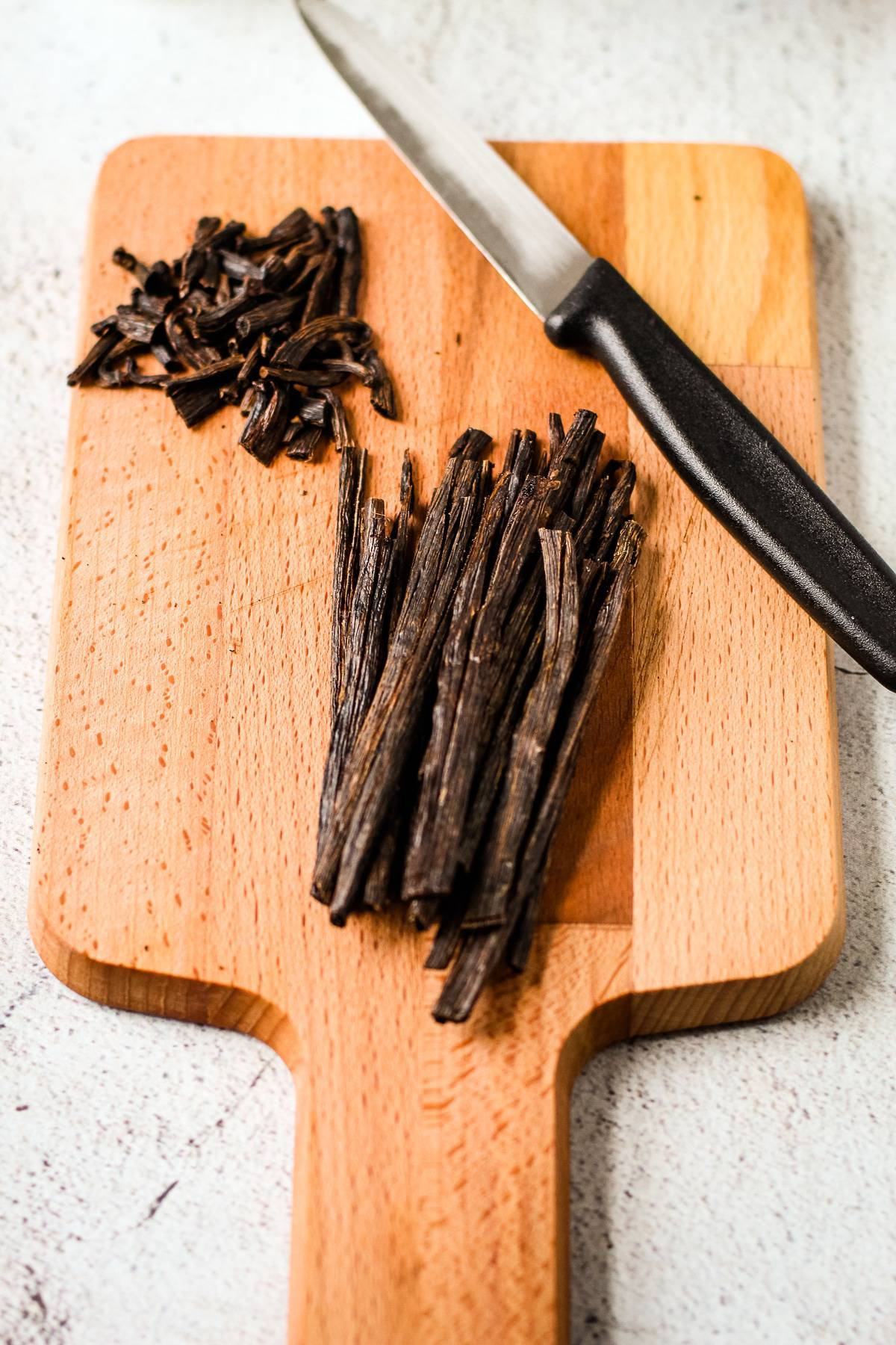 Cut vanilla beans on a cutting board.