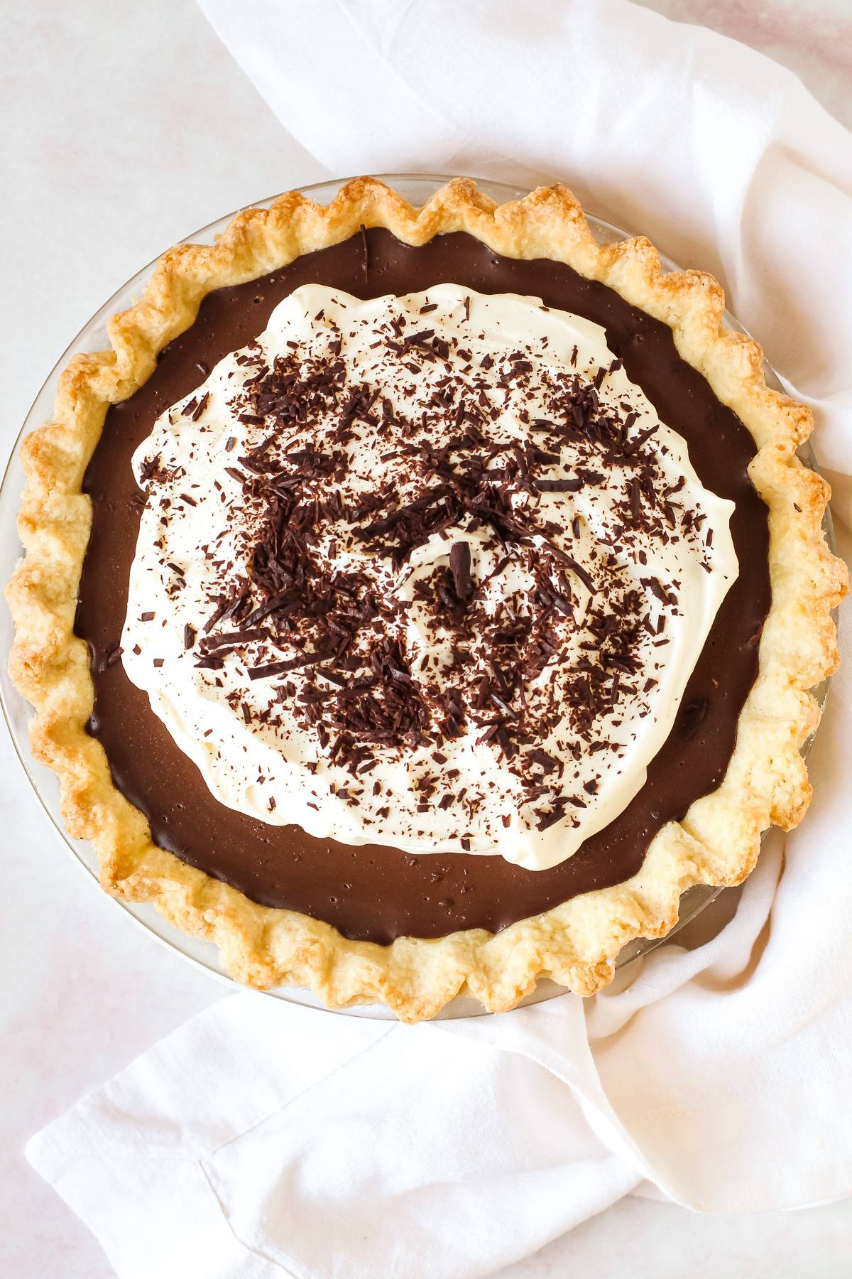 A whole chocolate cream pie with chopped chocolate on top of it.
