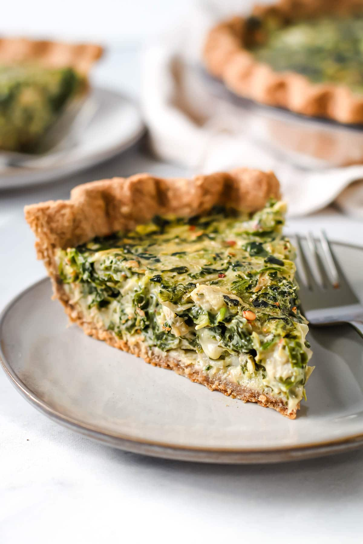 Slice of spinach artichoke quiche on a plate.