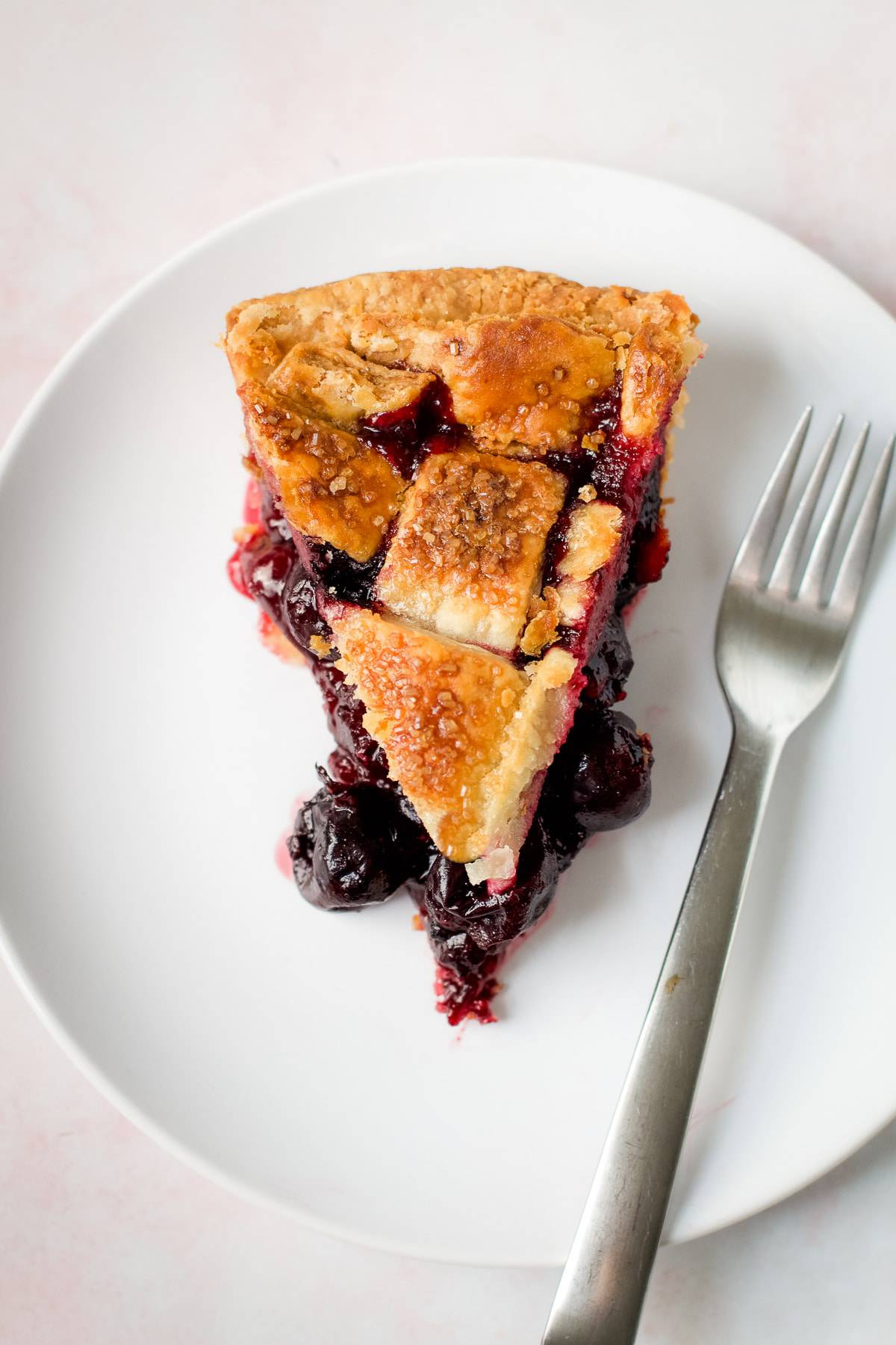 A slice of sweet cherry pie on a plate.