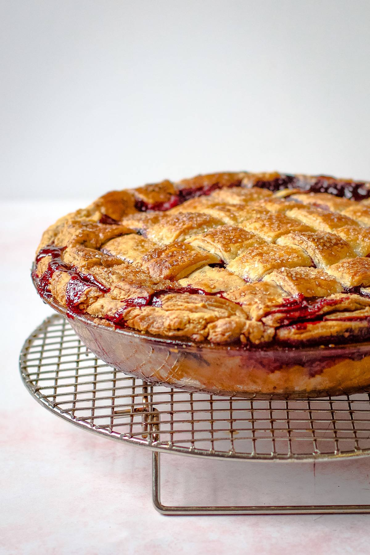 A lattice frozen cherry pie sitting on a cooling rack.