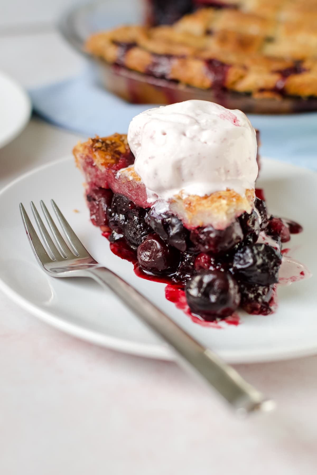 A juicy cherry pie with ice cream slightly melted on top of it.