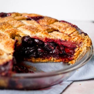 A whole sweet cherry pie with a slice taken out of it.