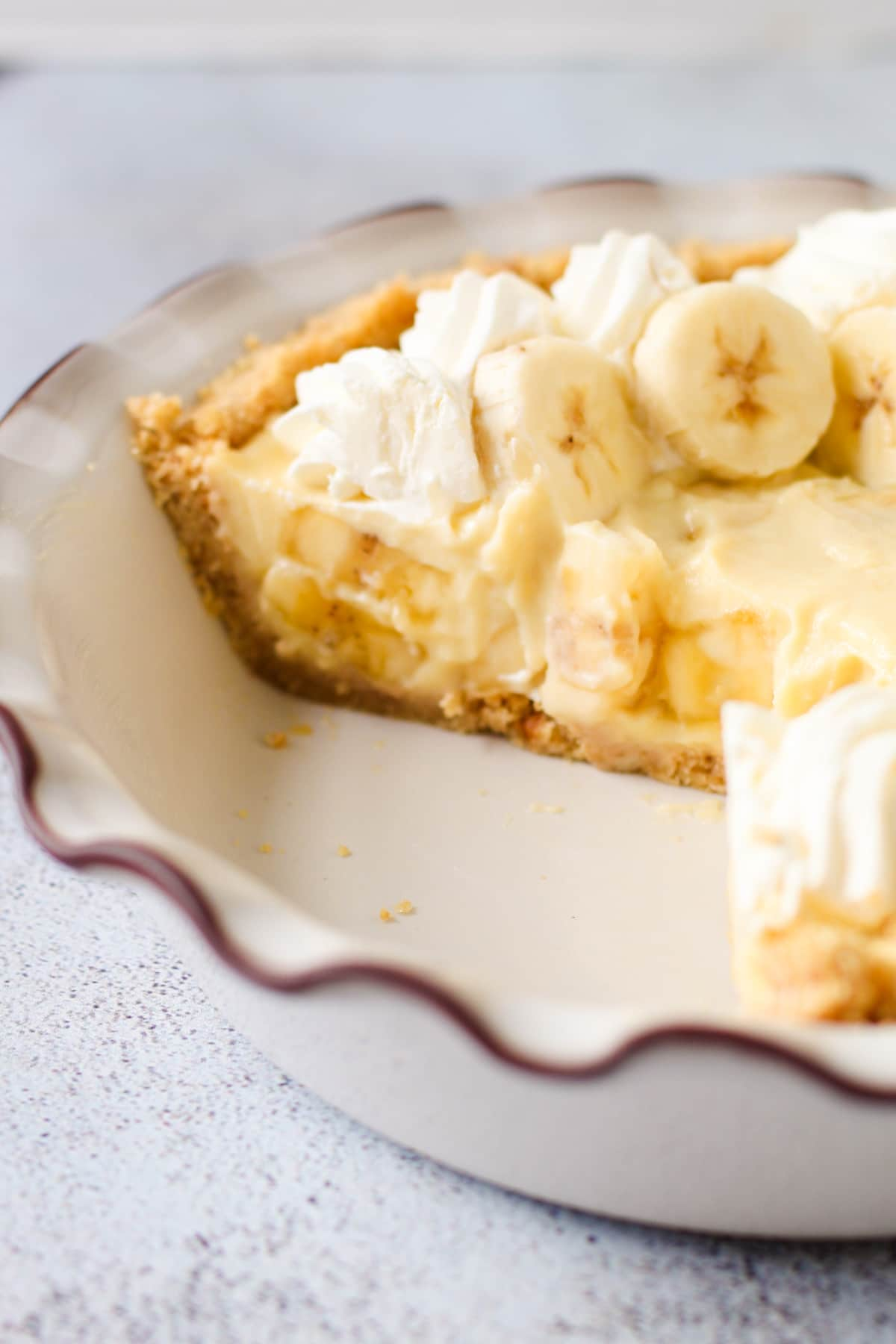 Banana cream pie with vanilla wafers in a pie plate.
