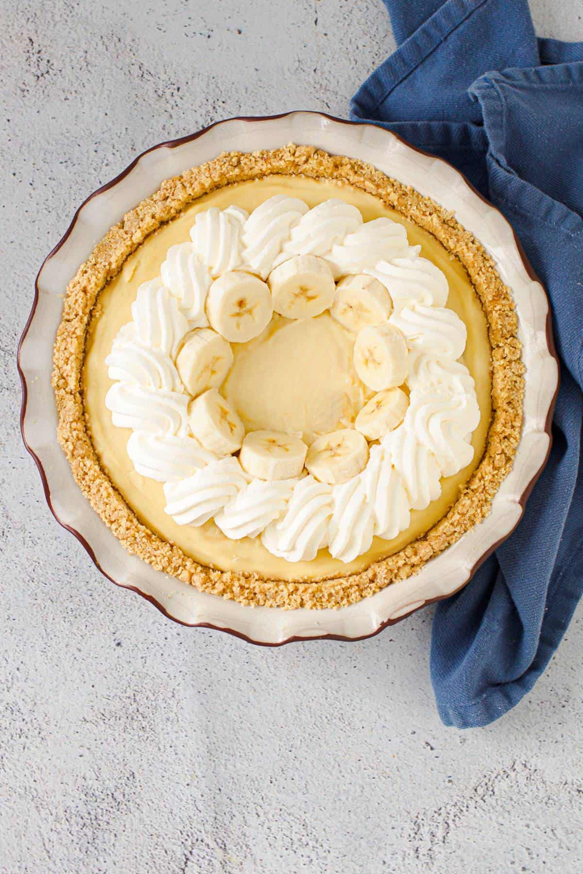 Homemade banana cream pie with whipped cream piping and fresh bananas.