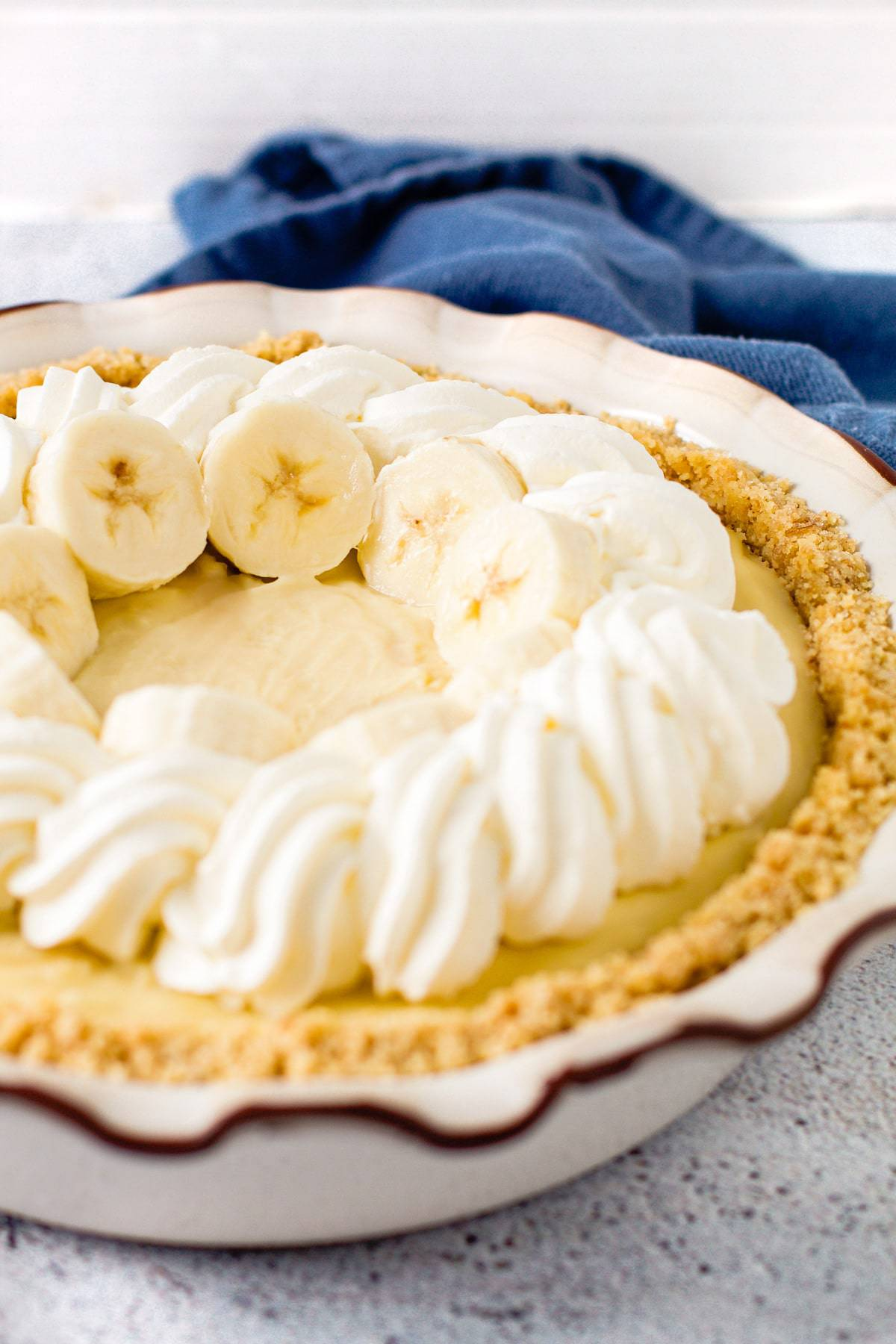 Fresh bananas lined up around the edge of banana cream pie.