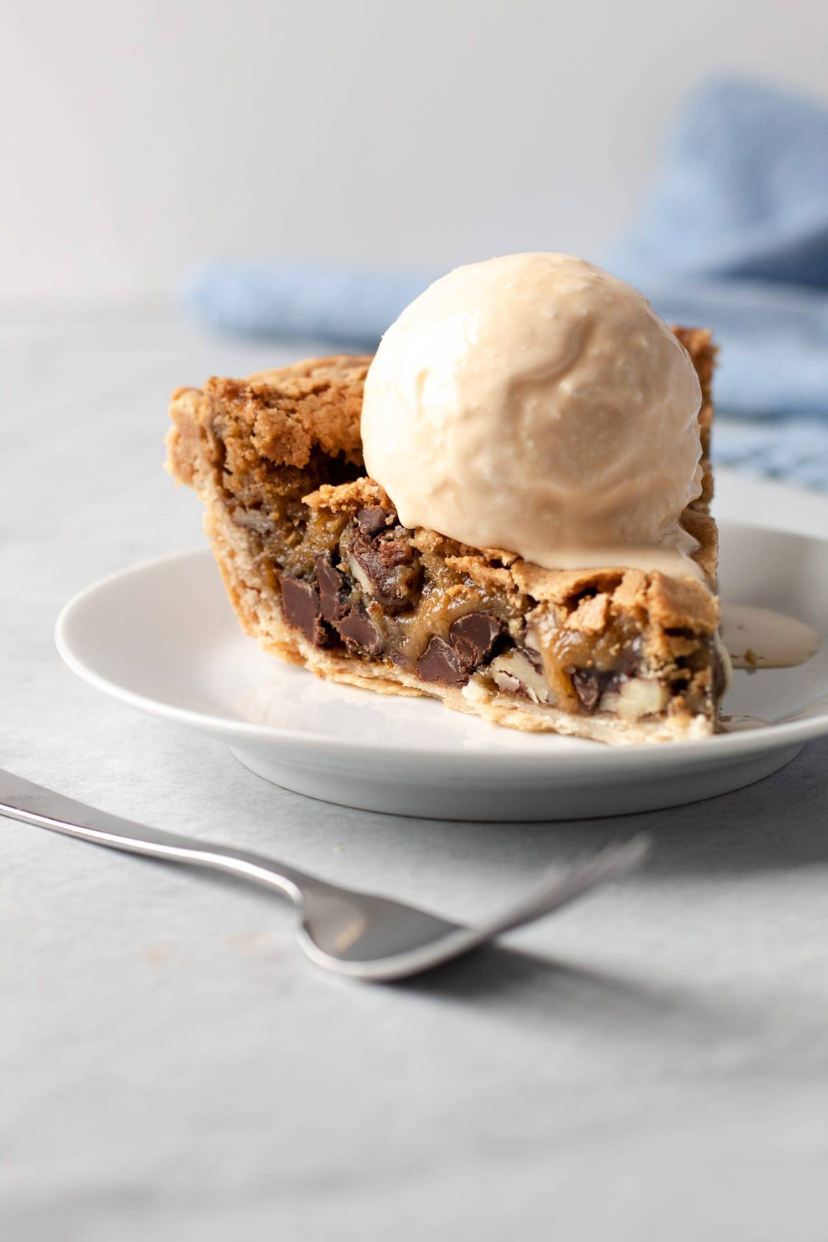 Chocolate chip cookie pie with a big scoop of melty vanilla ice cream on a plate.