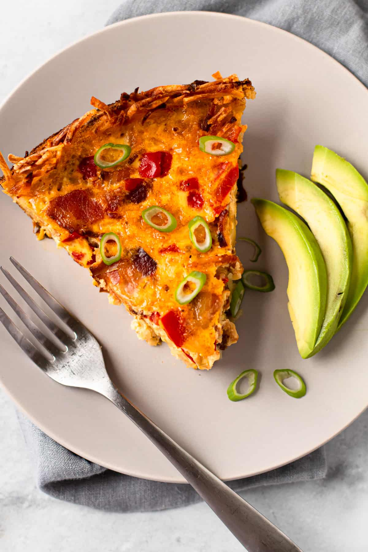 A slice of breakfast pie on a place with a fork and avocado.