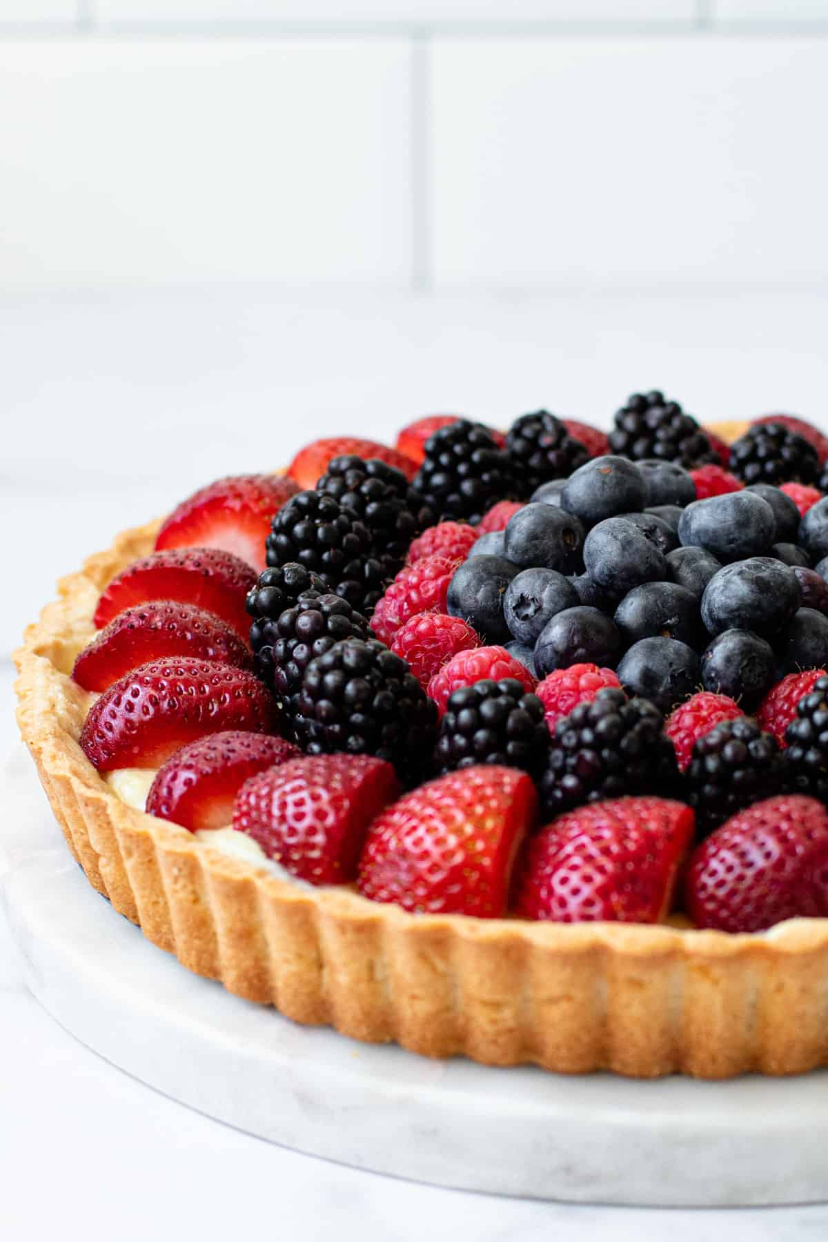 A side view of a classic fruit tart.