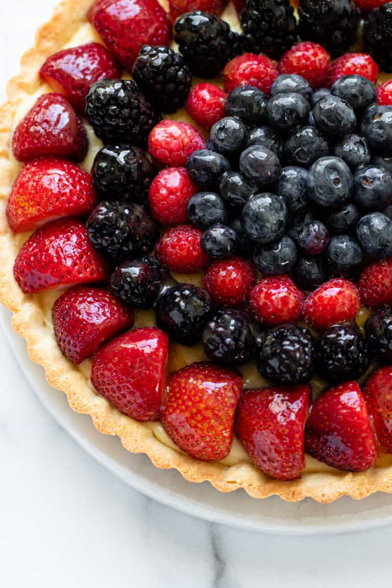 A glazed fresh fruit tart filled to the top with berries.