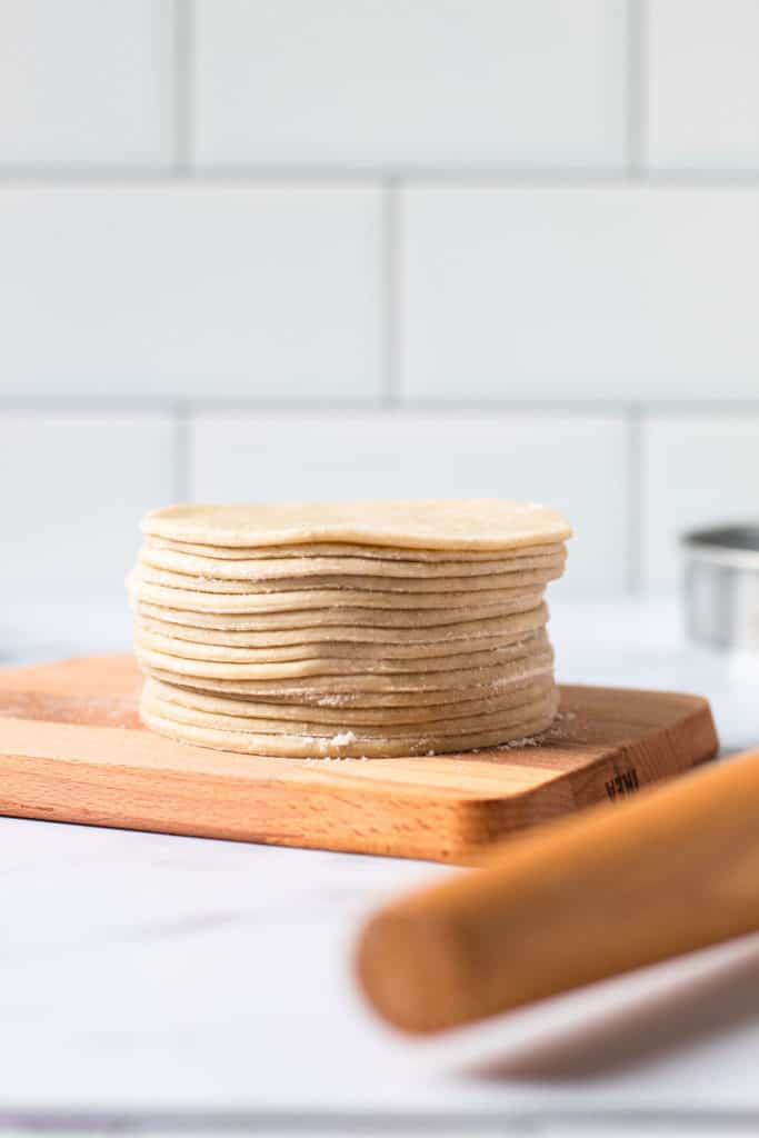 Dough cut into circles and stacked on top of each other for hand pies.