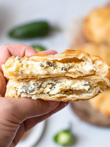 Jalapeno popper hand pies broken in half to expose the filling.