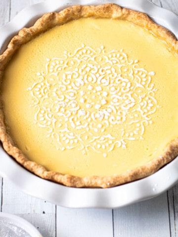Lemon Custard Pie with a powdered sugar decorative design.