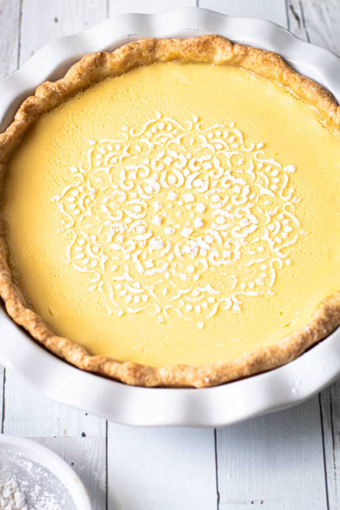 Lemon Custard Pie with a powdered sugar decorative design.
