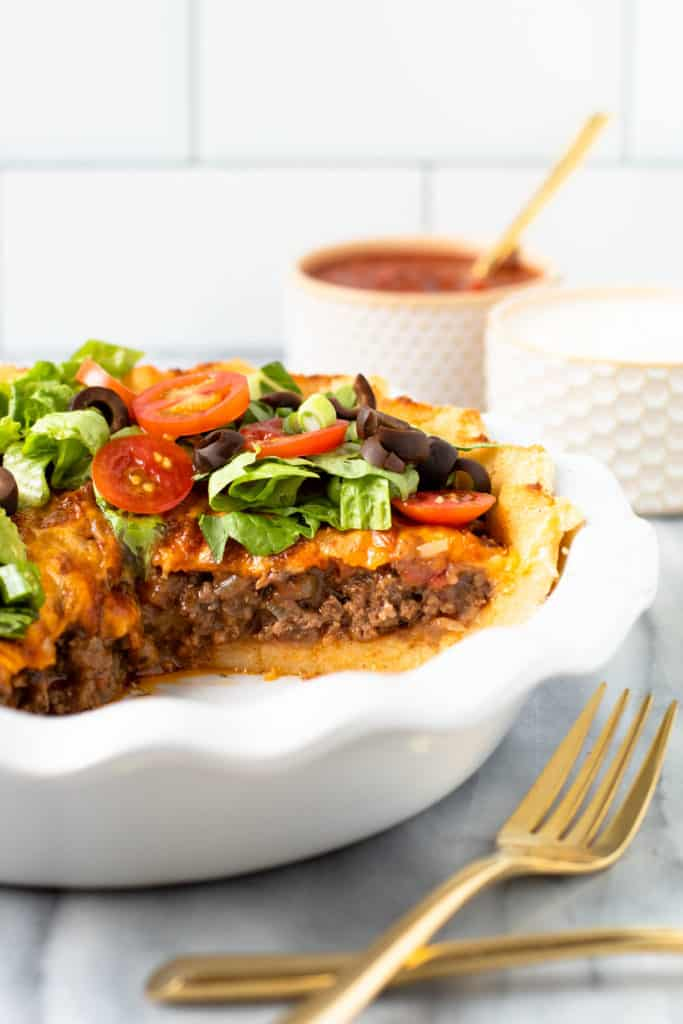 Beef taco pie with a slice taken out of it.