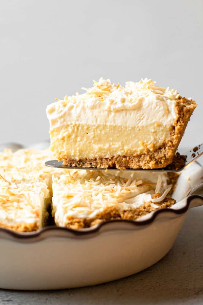 A slice of coconut cream pie being lifted from the pie plate.