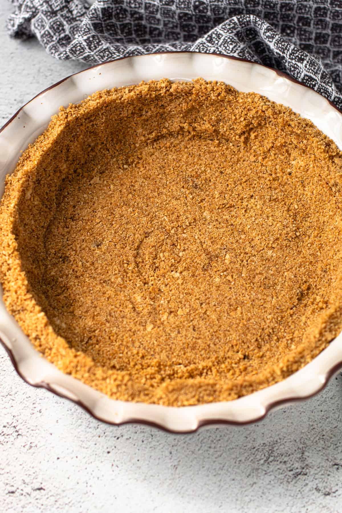 A graham cracker crust in a pie plate.