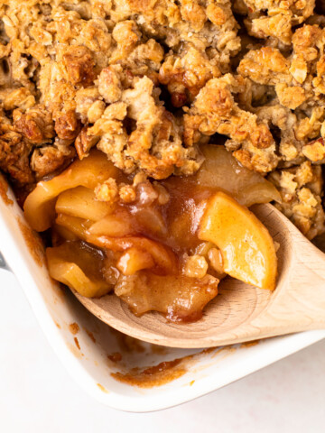 A scoop of healthy apple crisp with pecan oat crumbles.