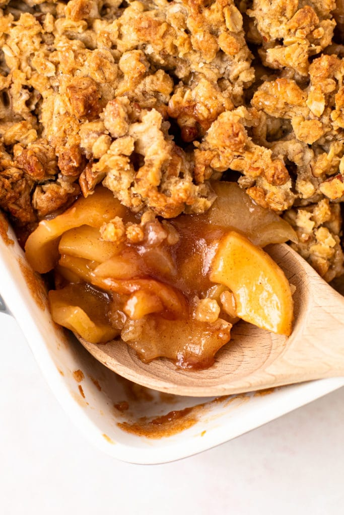A scoop of healthy apple crisp with pecan oat crumbles.