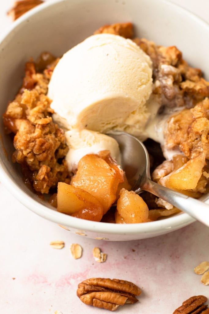 A bowl of healthy apple crisp with a scoop of vanilla ice cream on it.
