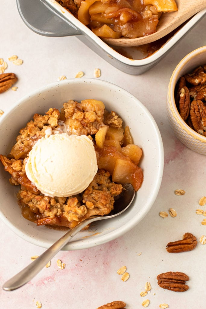 A bowl of apple crisp with vanilla ice cream on top.