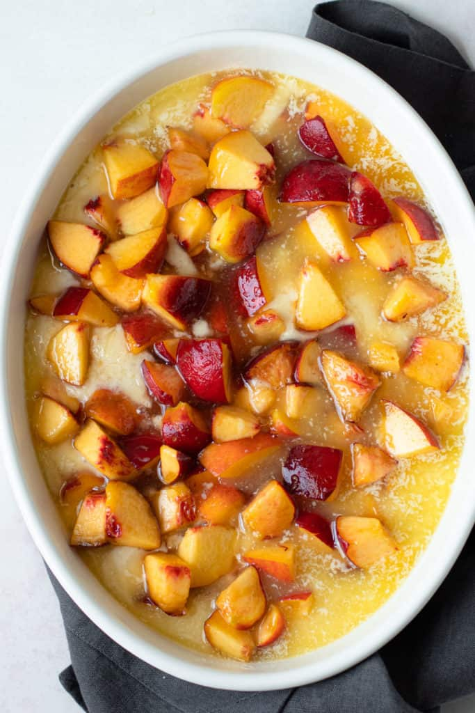 Peaches cobbler batter, melted butter and with fresh peaches on top.
