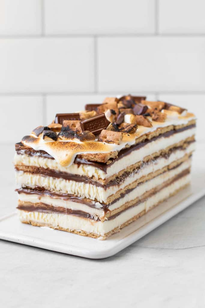 A S'mores Ice Box Cake on a platter with graham crackers and marshmallows on top.