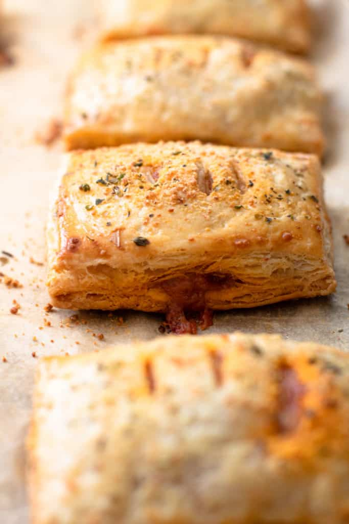 Baked pizza hand pies on a sheet tray.