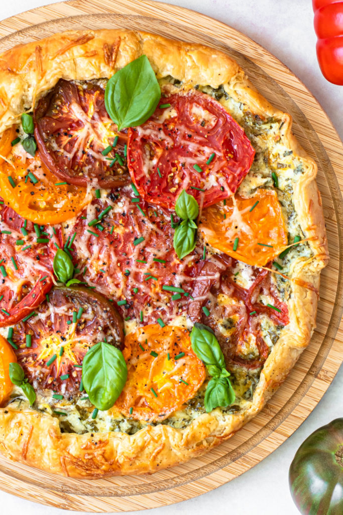 A baked tomato galette with herbs on top.