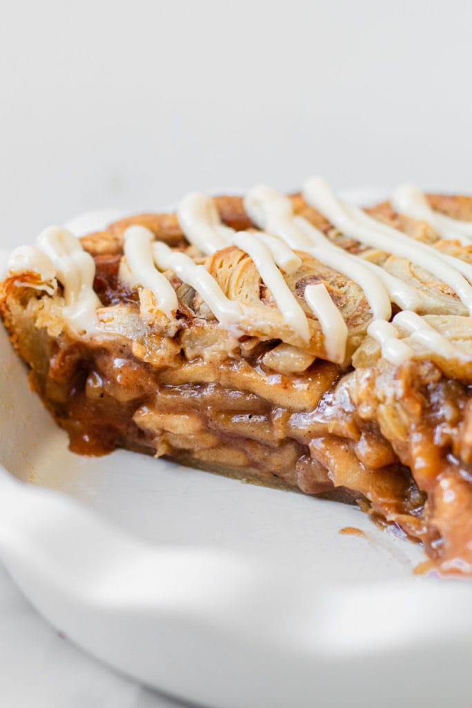 A profile view of cinnamon roll apple pie.