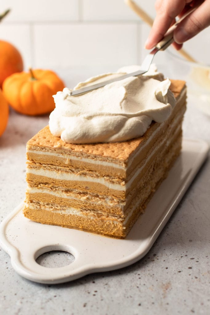 A no bake pumpkin layer cake being covered in whipped cream.