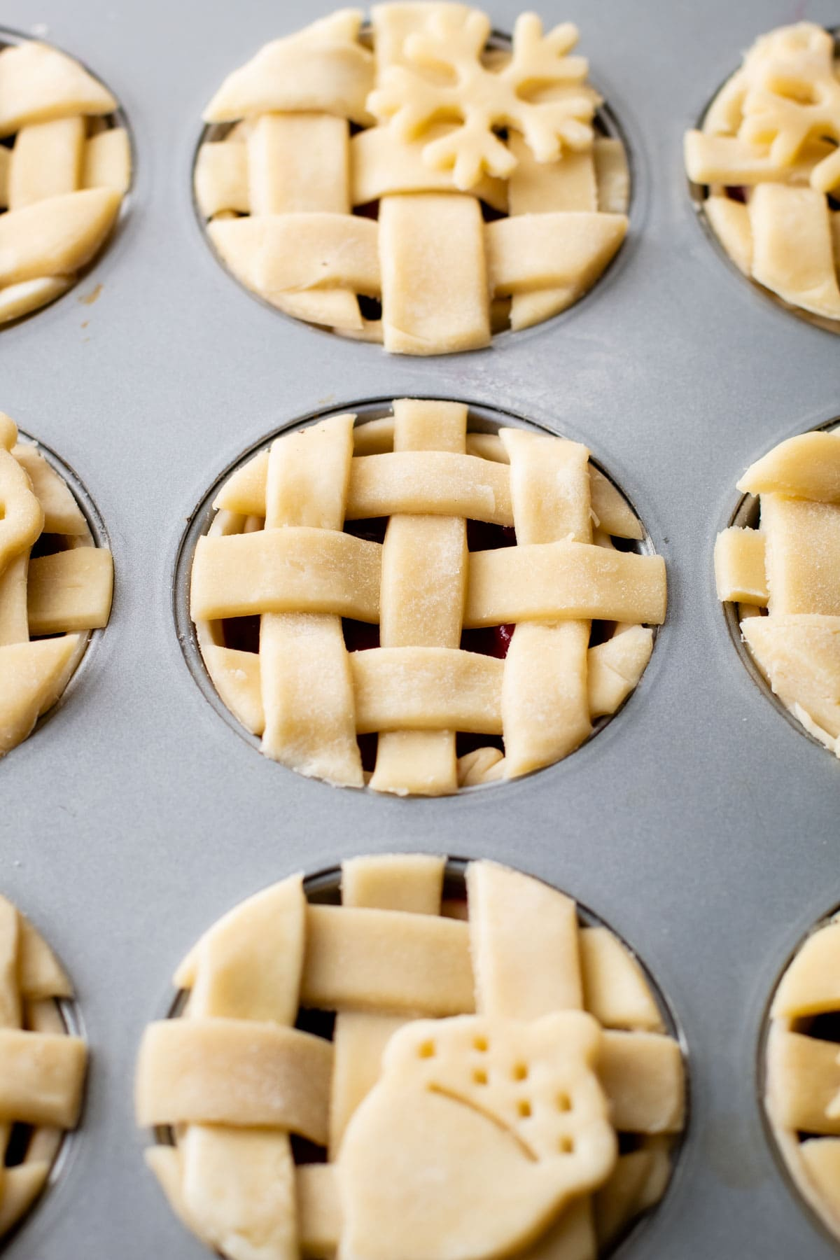 Mini cranberry pear pies unbaked in a muffin tin.