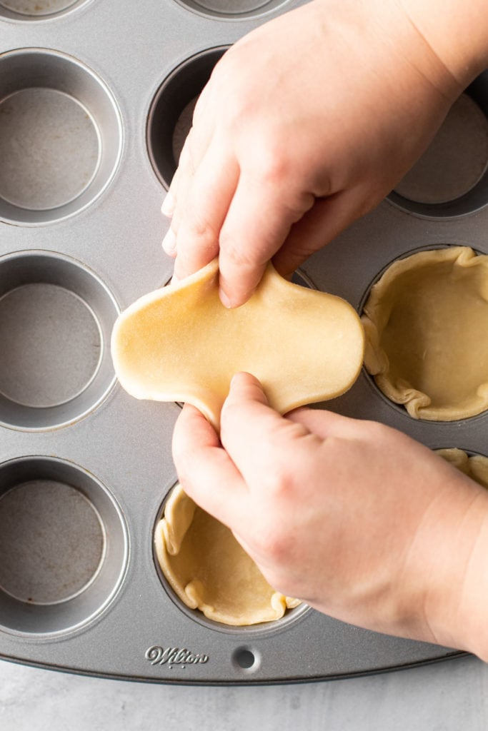 Placing dough into a muffin tin for mini pies.