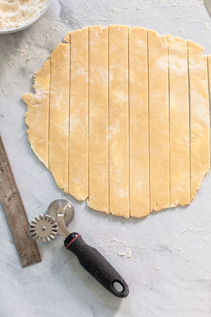 Cutting strips of dough to make a lattice.