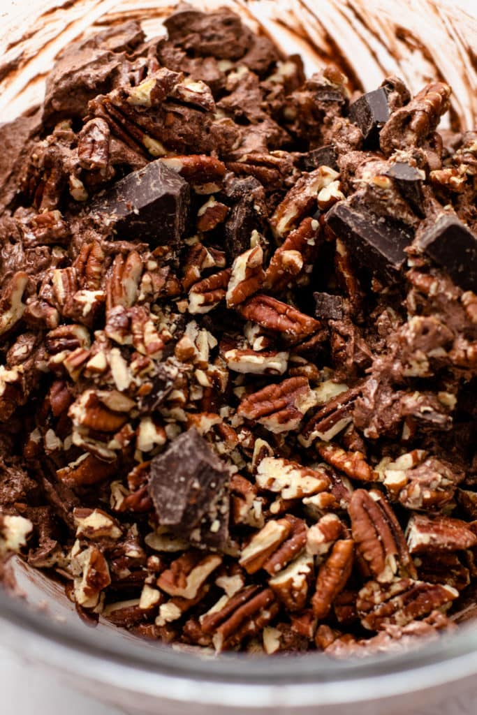Brownie pecan pie batter with chunks of chocolate and chopped pecans.