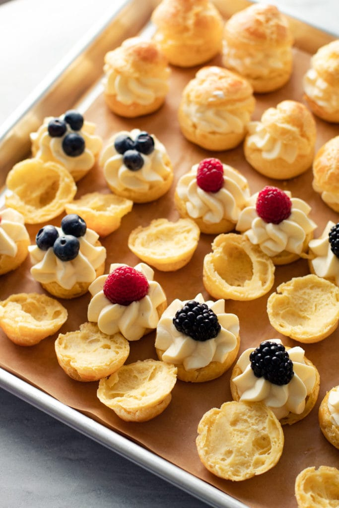 Cream puffs being filled with diplomat cream and fruit.